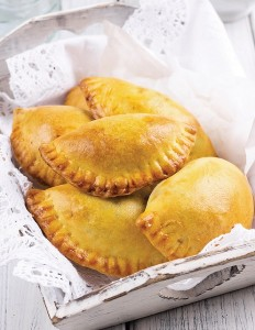 Empanadas De Viento combines gooey cheese and onions inside a crispy fried empanada that is topped with powdered sugar.