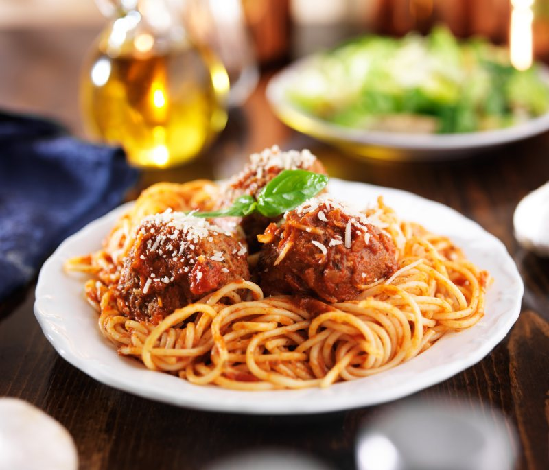 Italian food - spaghetti and meatballs at a dinner table.
