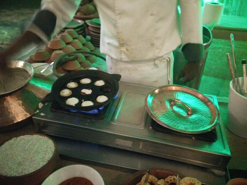 The chef makes paniyarams (little fried balls, made in a vessel with multiple round moulds) and serves them with coconut and tomato chutneys.