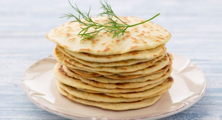 Flat bread with dill on a blue wooden background, selective focus